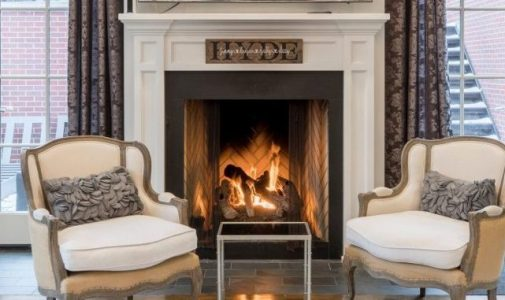 Shown is a cleaned white and gray fireplace, with a roaring fire, in a nicely decorated Buffalo living room